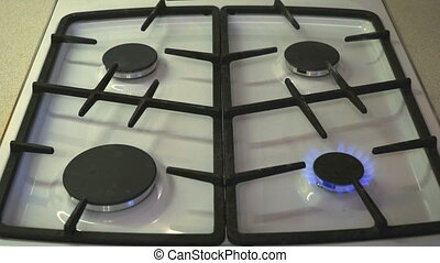 Four gas burners burn blue flame on a gas stove They light...