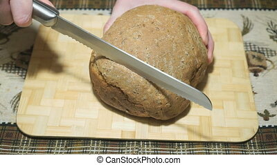 Rye-wheat bread is cut with a knife on a board
