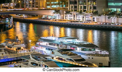View of Dubai Marina Towers and yachts in canal in Dubai night timelapse