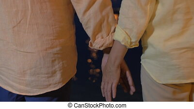 Close-up of man and woman holding hands at sea