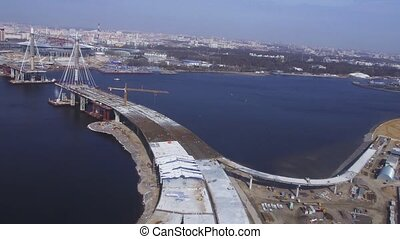 Aerial view from helicopter fly above water. Bridge under construction. River. Sunny day. Cityscape