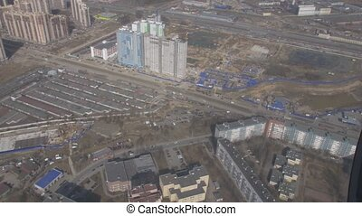 Aerial view from flying helicopter. Camera inside. Landscape city. Construction site of skyscrapers