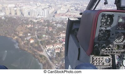 Pilot cabin in moment of fly helicopter above city. Control system. Camera inside. Transportation