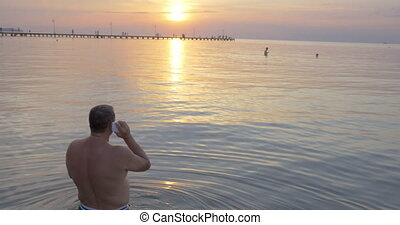 Back view of man talking over phone while watching sunset....