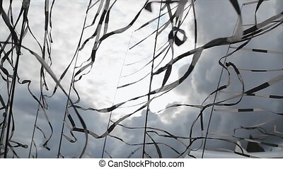 Many black and white tapes sway from wind in summer day Grey...