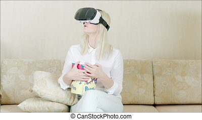 Woman using VR glasses sitting on the sofa - Steadicam shot...