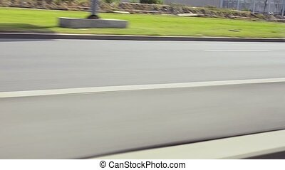 View on road inside driving car. Green grass. Movement. Journey. Summer sunny day. High speed