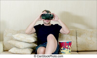 Man using VR glasses sitting on the sofa - Steadicam shot of...