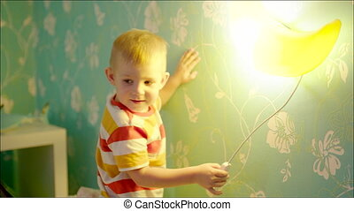 Little boy turning on and off bedside lamp - Shot of little...