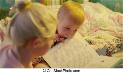Mum reading bedtime book to her son - Close up shot of...