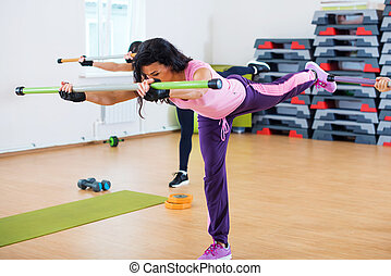 Group of people excercising with fitbars at fitness club.