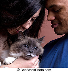 woman kissing a cat with her man