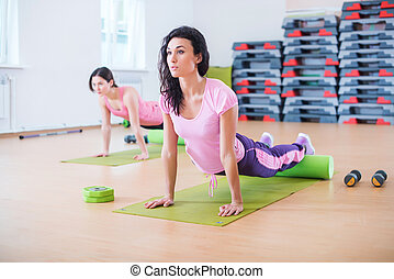 Fit woman doing pilates exercises stretching arching her...