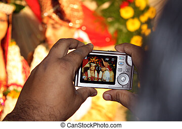 Wedding Photography - Two hands holding a small digital...