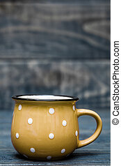 Yellow Ceramic Mug with White Dots on Blue Wooden Background