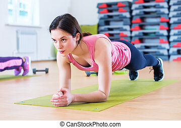 Fit sportive woman doing plank core exercise training back...