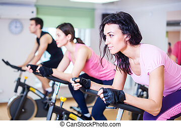 Group training people biking in the gym, exercising legs...