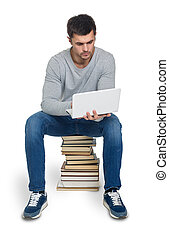 Young man with books and computer - Young man looking for...