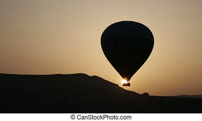 Balloons fly against the sun during sunrise, Cappadocia