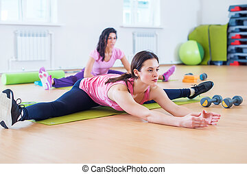 Woman doing cross split exercise working out her hip...
