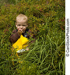 Toddler (one year old) sitting in a forest eating bilberries...
