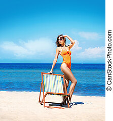 Young and sexy woman in a deckchair on the beach - Hot,...