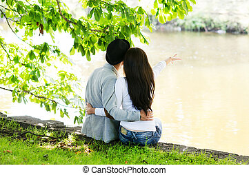 Young man and woman dating in the nature hugging each other