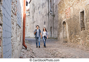 Young couple walking down a medieval street - Young...