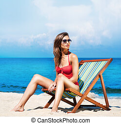 Young and sexy woman in a deckchair on the beach -...