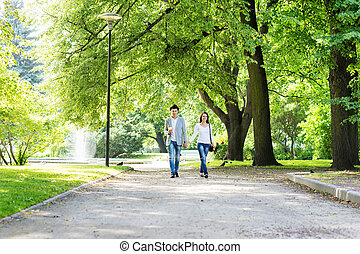 Young beautiful couple having a date in the park
