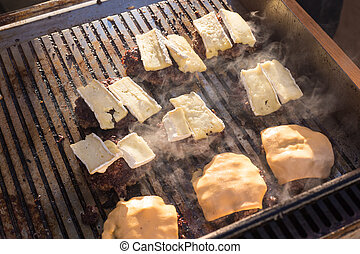 Beef burgers being grilled on barbecue. - Beef burgers being...