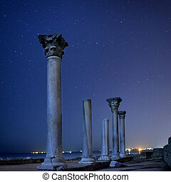 Ruins of ancient city columns under night sky - Ruins of...