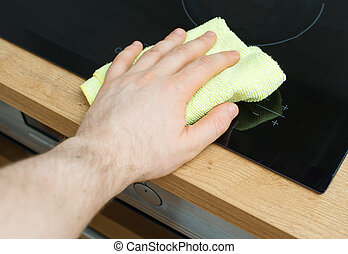 Man and 39;s hand wipes cooktop in the kitchen - Man39;s...