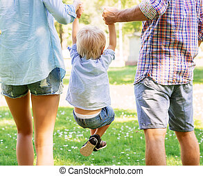 Mother and father holding their son in the park