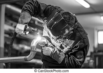 Industrial worker welding in metal factory - Industrial...