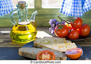 Bread with tomato and oil by a window