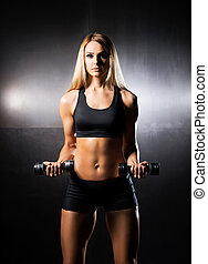 Athletic, fit and sporty girl training with dumbbells -...