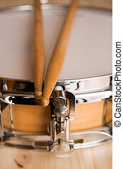 Drum sticks over a snare drum with wood background