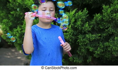 Cute kids blowing a soap bubbles in park