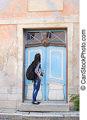 Attractive young female tourist opening door to a hostel