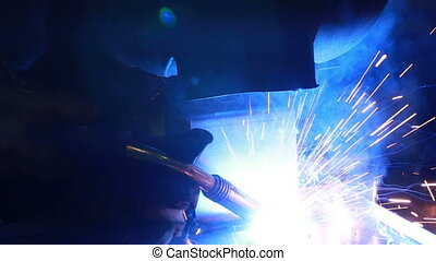 Worker with protective mask welding metal. Welder at the...