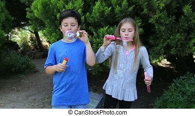 Kids blowing bubbles - Kids blowing a soap bubbles in park