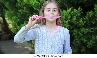 Cute little girl is blowing a soap