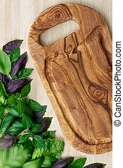 Heirloom basil on wooden table next to olive wood cutboard,...