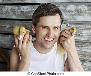 man with ducklings - young handsome farmer with two...