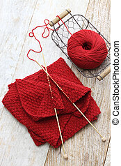 hand knitted red scarf, yarn ball and knitting needles,...