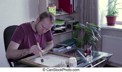 Man paints a canvas of white primer - Man with a brush on...
