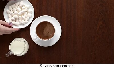 Adding marsh mallow into coffee on wooden background.
