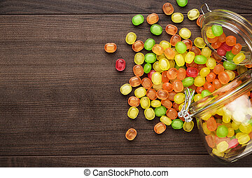 overturned glass jar full of colorful sweets - toppled over...