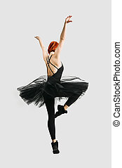 Beautiful ballerina wearing black tutu dancing on gray...